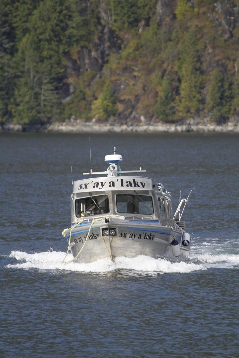 A boat with text printed on its nose and above its front windows. Text reads: sx'ay a'lakv