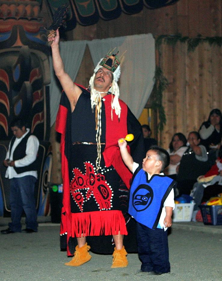 An adult and a child dancing and wearing regalia