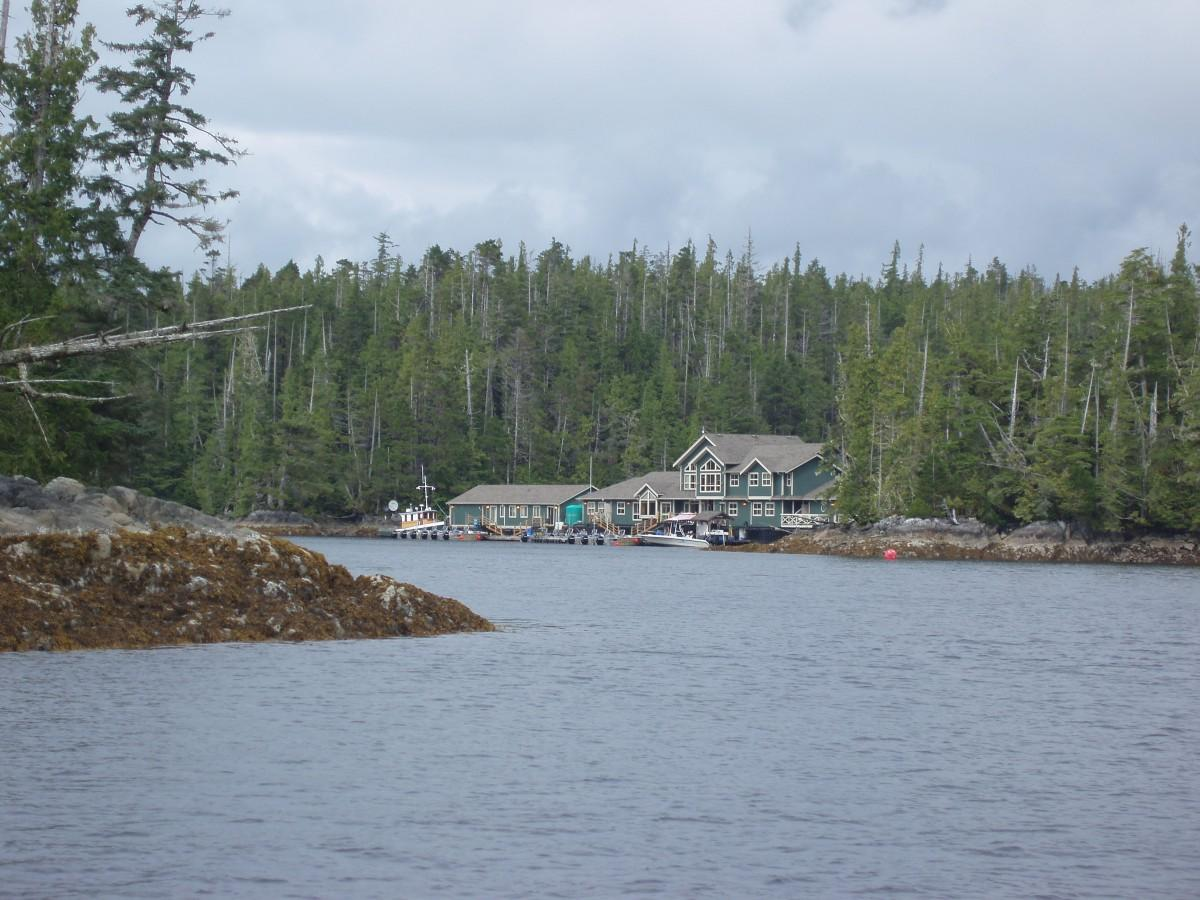 A fishing lodge with water in the foreground and trees in the background
