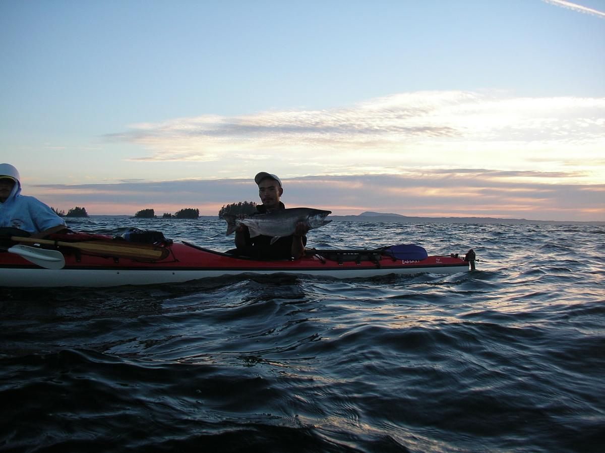 A sport fisher in a kayak, holding a fish at chest level