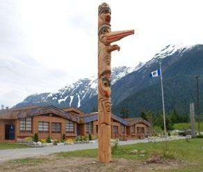 A totem pole near a path with buildings and a flag in the background