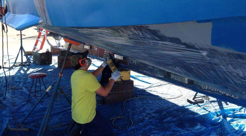 Glen Clellamin refinishing the hull of his boat in preparation for the fishing season.