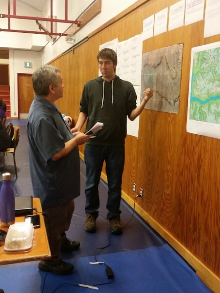 Clyde Tallio speaking with Peter Tallio while looking at some maps