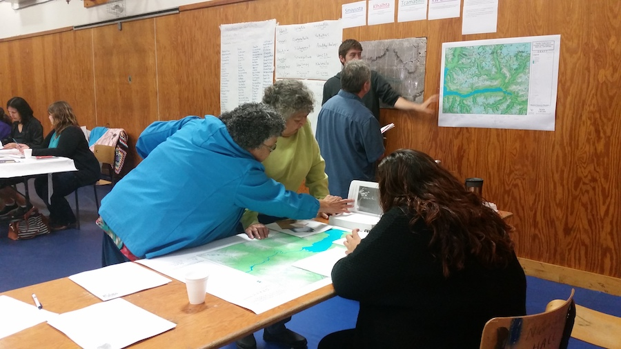 Grace Hans and Caroline Mack reviewing Nuxalk place name maps on a table