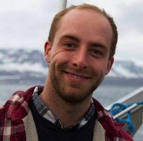A headshot of Jean who has blonde hair and beard, a red plaid shirt, and is smiling with his teeth showing. The background is a grey sky and snowy mountains. The metal rim and ropes directly behind him suggest he's on a boat.