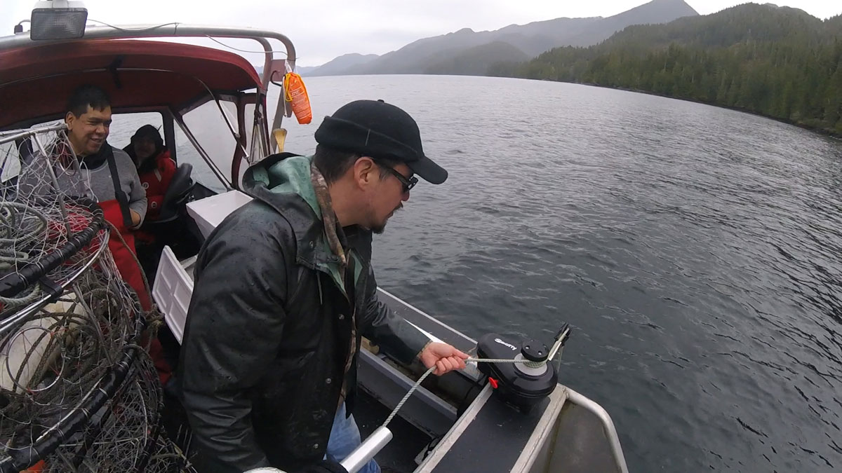 A man in a dark raincoat and cap is looking over the side of a boat, and there are two men behind him also on the boat. The water looks grey, and there are trees in the distance on the right.