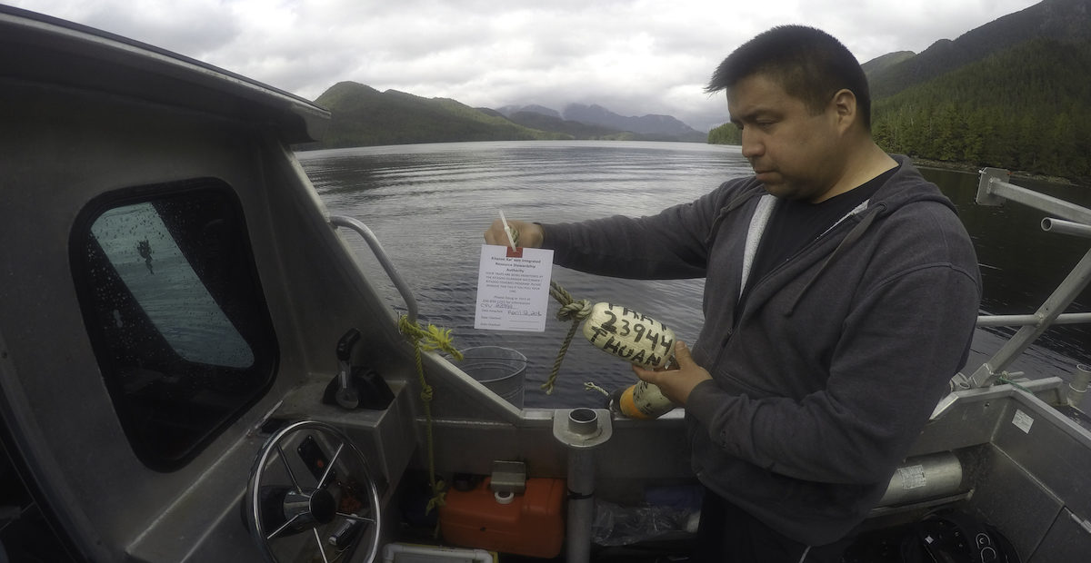 Guardian Watchman Ernie Mason labeling crab traps.